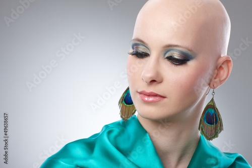 Portrait of hairless woman in turquoise silk dress