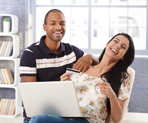 Happy couple online shopping at home laughing