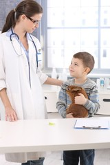 Vet and smiling kid with pet rabbit