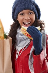 Winter portrait of afro woman with sandwich