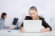lächelnde frau mit laptop im büro