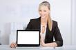 lächelnde mitarbeiterin präsentiert am laptop