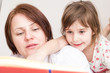 A mother and her little daughter reading a book before sleeping