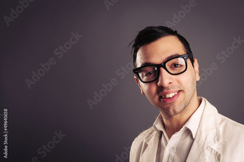 Funny portrait of young nerd with eyeglasses on grey background.