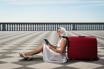 Retro woman with sunglasses and suitcase reading book portrait