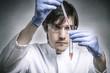 Forscher verwendet Pipette mit roter Flüssigkeit