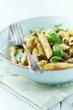 Bowl of penne pasta with basil pesto and capers