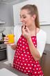 Junge Frau trinkt in der Küche Orangensaft