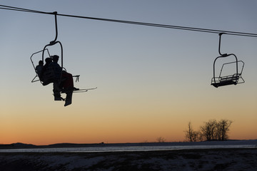 Skiers and snowboarders on chair lift at sunset