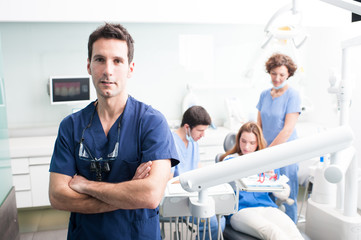 A portrait of a dentist with his team working in the background