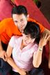 Asian couple at home on sofa