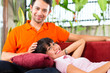 Asian couple in spacious home on sofa
