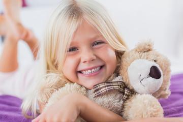 Blonde girl embracing her teddy bear