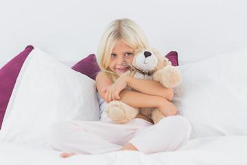 Little girl embracing her teddy bear