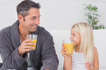 Father and his daughter drinking glass of orange juice