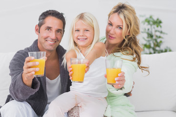 Family holding glasses of orange juice