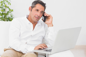 Man using laptop and cellphone