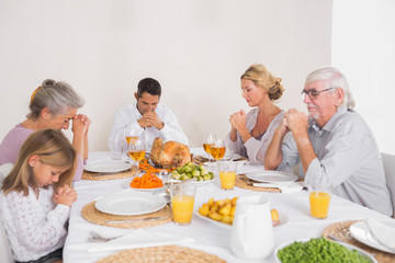Family saying grace before eating a turkey