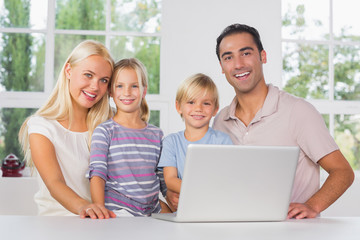 Happy family using a laptop together