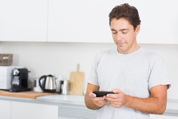 Man texting in the kitchen