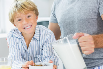 Smiling boy having cereal with father pouring milk