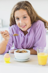 Young girl having cereal for breakfast