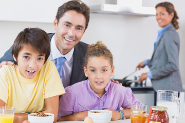 Father and children having breakfast