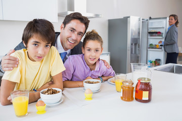 Smiling father and children having breakfast