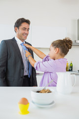 Daughter fixing fathers tie