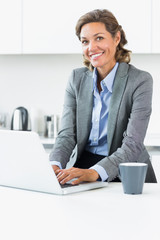 Woman typing on laptop in the kitchen before work