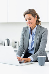 Happy woman typing on laptop