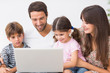 Smiling family using laptop on couch