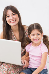 Mother and daughter happily using laptop