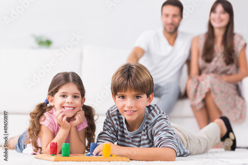 Happy siblings playing board game on floor