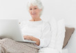 Smiling elderly woman typing on her laptop
