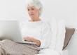 Elderly woman typing on her laptop