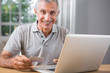 Smiling mature man using his laptop