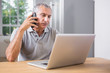 Mature man using his laptop and calling