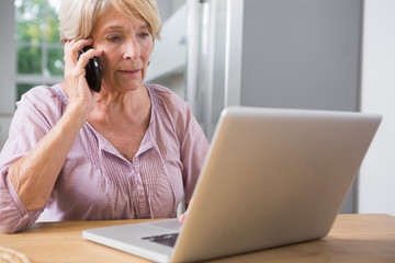 Focused woman using her laptop and calling