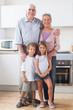 Children standing with grandparents in kitchen