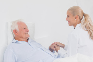 Doctor comforting elderly patient