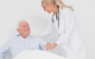 Doctor helping elderly man to sit up