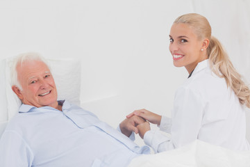 Smiling doctor holding hand of patient