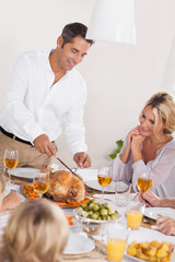 Father carving the turkey at the head of the table