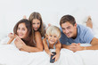Family lying on the bed with a remote