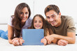 Family with tablet lying on a carpet