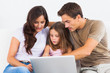 Family sitting on a sofa with the laptop