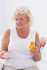 Smiling aged woman with the opened pill bottle