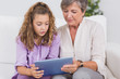 Child and her grandmother holding tablet pc