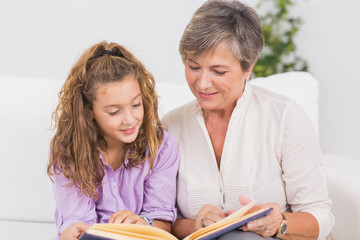 Portrait of a child and her grandmother reading a book